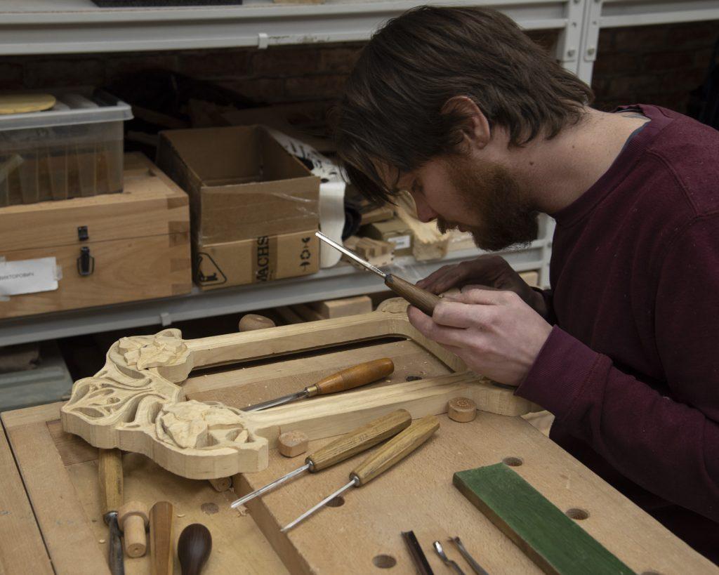 Евгений за резьбой деревянной рамы